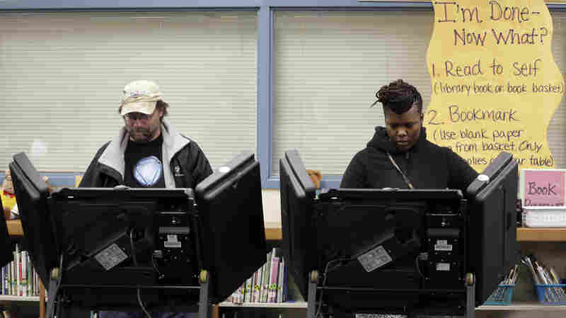Rich Baranowski (left) and Tracy Hardy vote Tuesday in the Ferguson, Mo., municipal election. Three of the city's six seats will now be filled by black council members.
