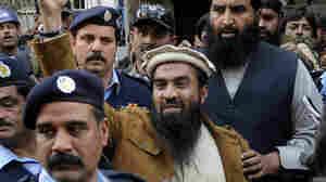 Zaki-ur Rehman Lakhvi, accused of plotting the 2008 Mumbai terror attacks, raises a fist outside a court in Islamabad, Pakistan, on Jan. 1. Lakhvi was released on bail Friday.