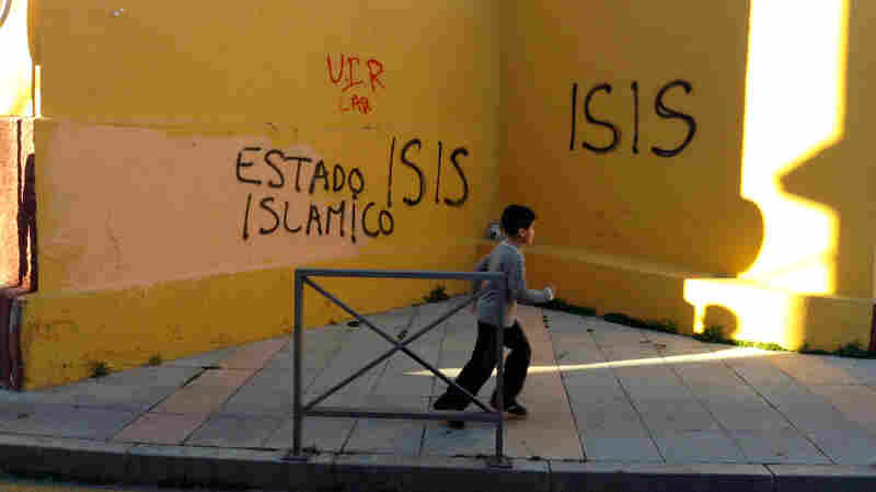 A young boy runs past graffiti that's supportive of the self-declared Islamic State in  a neighborhood in Ceuta. Analysts say a mix of religion, poverty and isolation have made Ceuta fertile ground for recruitment by the Islamic State.