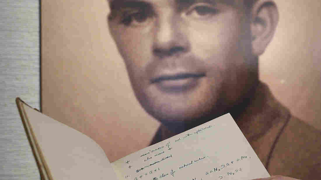 A page from the notebook of World War II code-breaking genius Alan Turing is displayed along with his portrait. The 56-page manuscript sold Monday for more than $1 million.