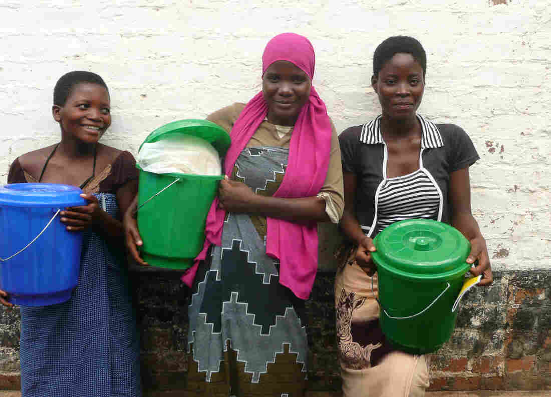 Three women in Malawi hold buckets of a fortified corn soy blend. Is this the right food for pregnant teens? Or is nutrition-rich peanut butter better?