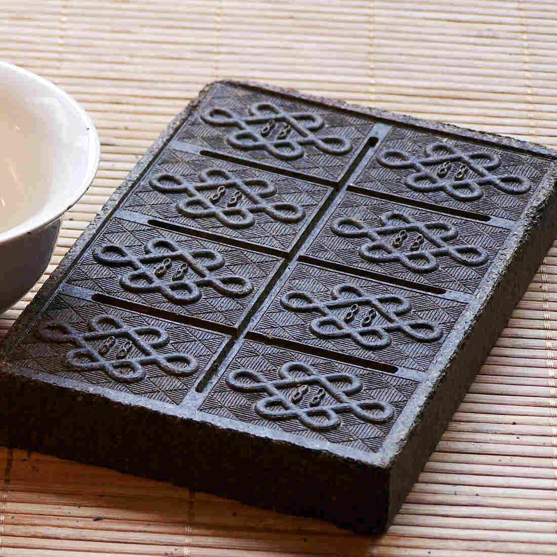 A modern-day tea brick, compressed and embossed with an intricate design. Before the 1500s, tea leaves came in bricks not unlike this one.
