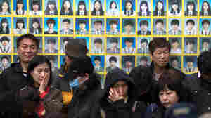 Relatives of victims of the Sewol ferry accident stand before a banner featuring victim photos during a protest. More than 300 people, most of them high school students, died in the accident. Nine people remain missing.