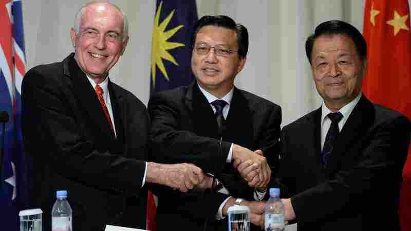 Australia's Deputy Prime Minister Warren Truss (left), Malaysia's Transport Minister Liow Tiong Lai (center) and Chinese Transport Minister Yang Chuantan shake hands after a news conference about Flight MH 370 on Thursday. The search zone for the missing Malaysia Airlines flight will be doubled if nothing is found in the huge undersea area now being scanned for wreckage.