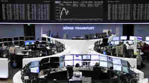 Traders are pictured at their desks in front of the DAX board at the Frankfurt stock exchange on Friday.