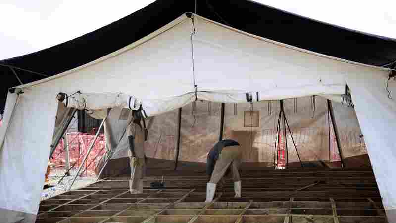 Liberian workers dismantle shelters in an Ebola treatment center in the Paynes Ville neighborhood of Monrovia. Doctors Without Borders closed the center last month because it was no longer needed.