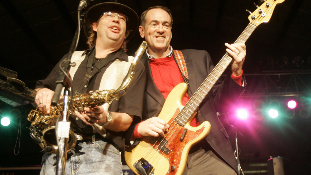 Huckabee (right) plays bass guitar with a member of the Boogiewoogers band at a rally in Iowa in 2008.