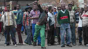 South African hostel dwellers demonstrate against foreigners in Johannesburg on Friday after overnight violence between locals and immigrants in the city.