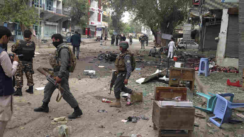 Afghan security forces inspect the site of a suicide attack near a new Kabul Bank in Jalalabad, Afghanistan, on Saturday.