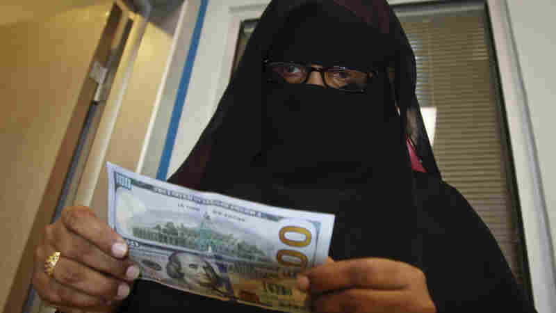 A Somali woman counts the cash she collected from a money transfer service in Mogadishu, the capital city.