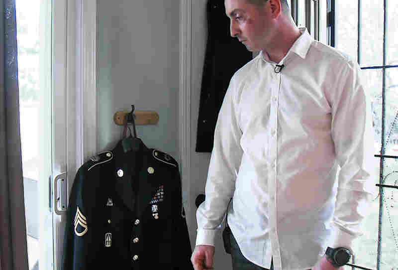 Rida Sihab Mansour, a staff sergeant in the National Guard, stands with the uniform he wears when he serves on the honor guard at military funerals. He says he's positive that his guard commitments are making it more difficult to build a career.