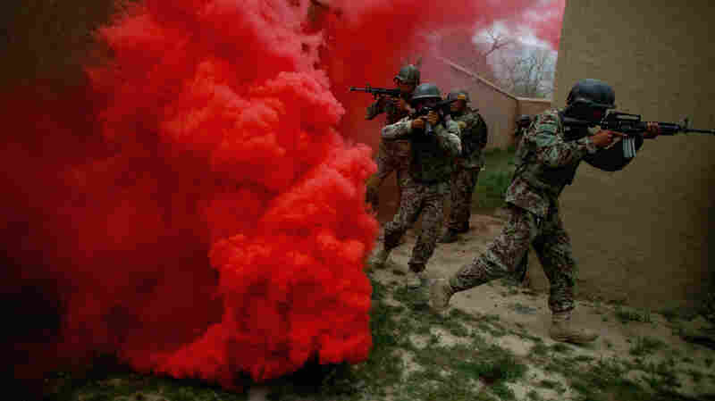 Afghan commandos move through a smoke screen during a training exercise at Camp Commando on the outskirts of Kabul. Afghanistan.