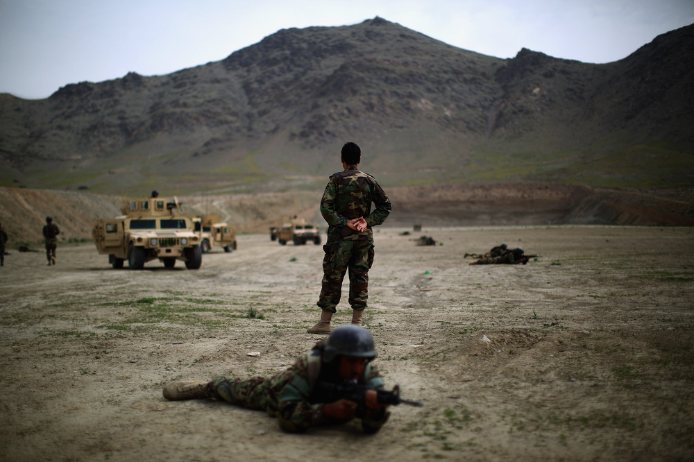 An Afghan commando instructor looks out over his troops during a training exercise.