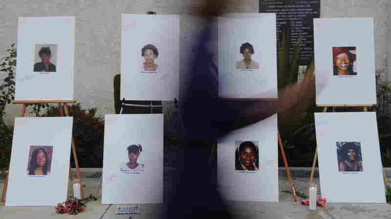 """A woman walks past a memorial for some of the victims who are said to have died at the hands of the serial killer dubbed the """"Grim Sleeper."""""""