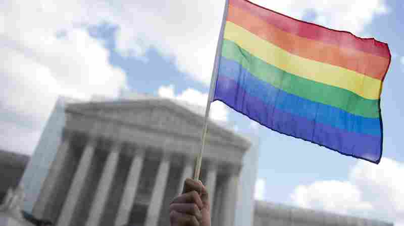 A same-sex marriage supporter waves a rainbow flag in front of theSupreme Court in 2013.
