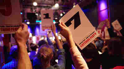 Guests hold up ratings cards at an All Songs Considered listening party in Boston.