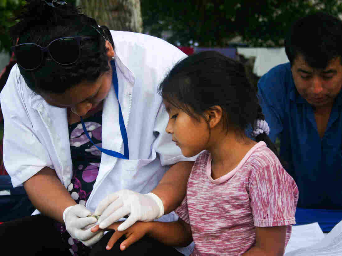 Nurse Sheena Balarezo draws blood from Linda Cutipo Ylaquijo, 6, as part of a huge health survey.