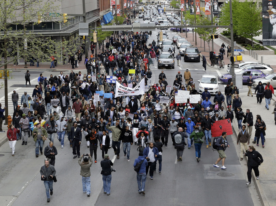 Earlier this week, protesters marched for Freddie Gray through downtown Baltimore. Gray died from spinal injuries about a week after he was arrested and transported in a police van. A larger protest is planned for Saturday afternoon. (Patrick Semansky/AP)