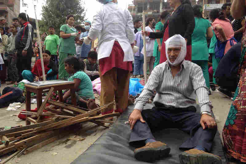 Injured people receive treatment outside the Medicare Hospital in Kathmandu, Nepal, on Saturday.