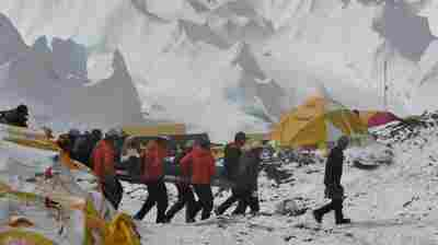 Rescue team personnel carry an injured person towards a waiting rescue helicopter at Everest Base Camp on Sunday.