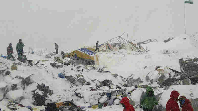 People approach the scene after an avalanche triggered by a massive earthquake swept across Everest Base Camp, Nepal on Saturday. At least 17 people have been killed on the mountain.