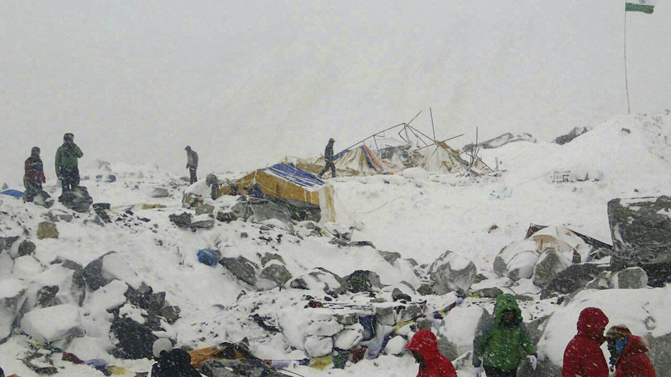 People approach the scene after an avalanche triggered by a massive earthquake swept across Everest Base Camp, Nepal on Saturday. At least 17 people have been killed on the mountain. (Azim Afif/AP)