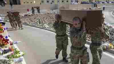 Soldiers in Malta carry coffins during a funeral service for 24 migrants who drowned while trying to reach southern Italy.