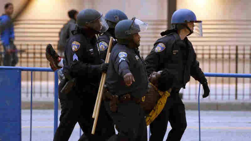 Police carry a detained man to a waiting police van after a march to City Hall for Freddie Gray, on Saturday. Authorities say 34 people were arrested in the protest over Gray, who died in police custody last week.