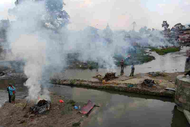 People burn the bodies of earthquake victims at a mass cremation at Pashupatinath in Kathmandu on Sunday.