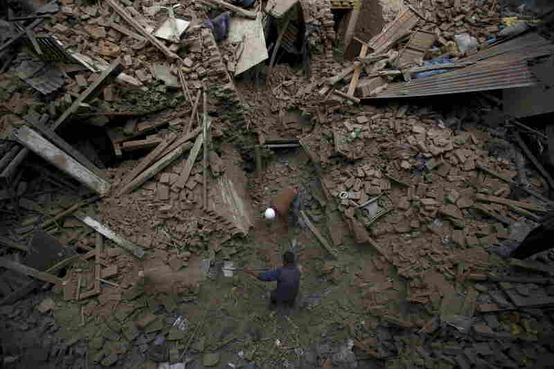 People search for family members trapped inside collapsed houses a day after an earthquake in Bhaktapur, Nepal on Sunday
