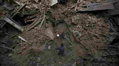 People search for family members trapped inside collapsed houses a day after an earthquake in Bhaktapur, Nepal on Sunday.