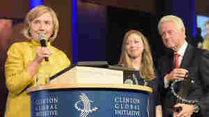 Former Secretary of State Hillary Clinton speaks at the Clinton foundation's Clinton Global Initiative conference with her husband, Bill, and daughter, Chelsea, looking on.