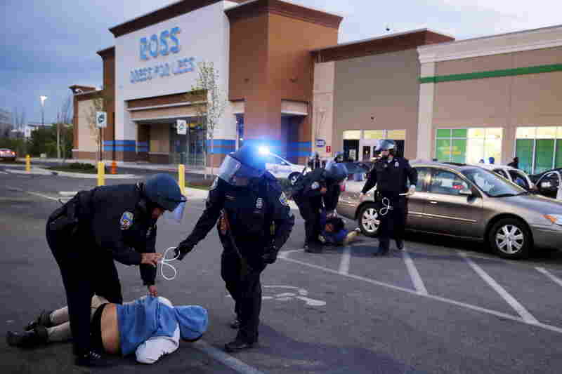 "Baltimore police officers arrest looters after they emerged from a ""Deals"" store with merchandise Monday evening in Baltimore."