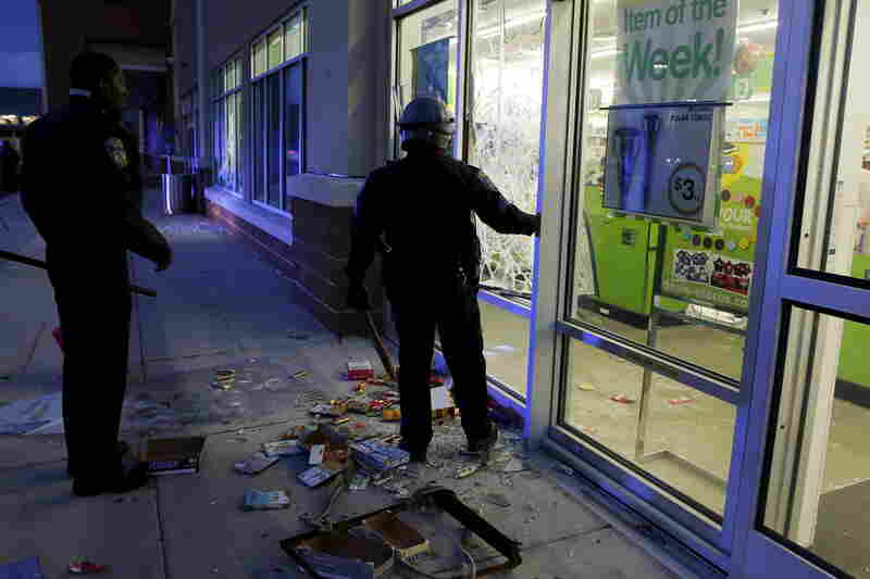 Baltimore police officers arrive as darkness falls in Baltimore at a store that was just vandalized and looted Monday by rioters.