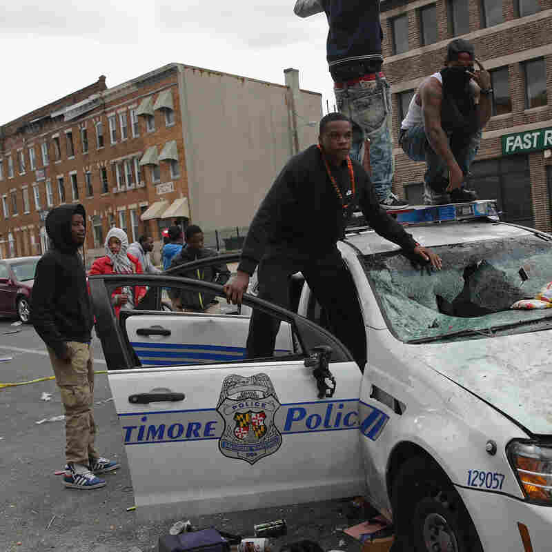 Demonstrators climb on a destroyed Baltimore Police car Monday furing violent protests following the funeral of Freddie Gray. The 25-year-old was arrested for possessing a switchblade April 12 outside a west Baltimore housing project, and died a week later in the hospital from a severe spinal cord injury he received while in police custody, according to his attorney.