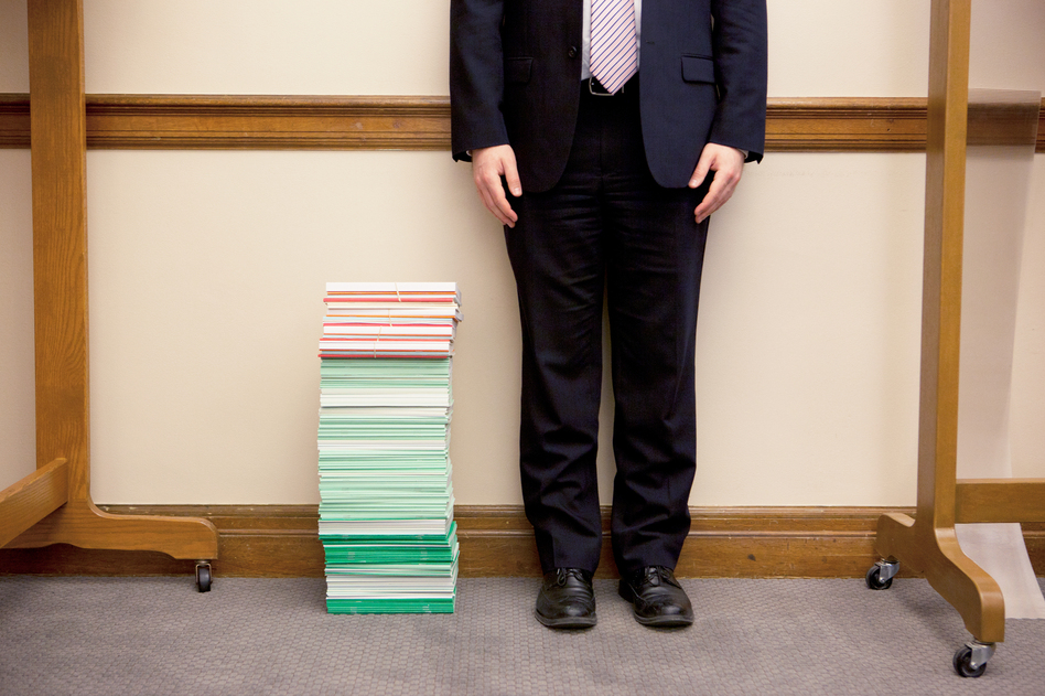 The stack of amicus briefs filed as of April 9 reached past the knee of NPR legal affairs intern Anthony Palmer. The briefs cost, on average, an estimated $25,000 to $50,000. (Emily Jan/NPR)