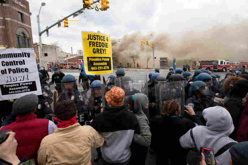 Police and protesters clash in front of a building that was set on fire as protests of the death of Freddie Gray continue in Baltimore, Maryland, on Monday.