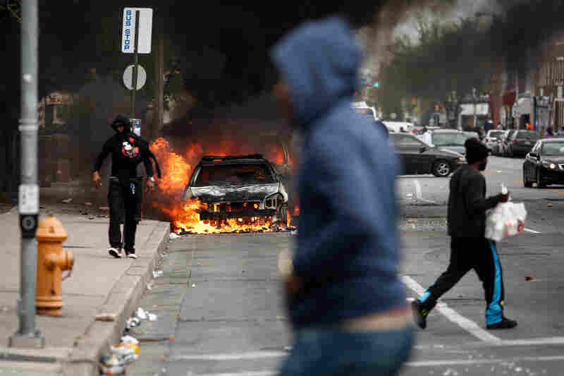 People walk past burning cars near the intersection of Pennsylvania Avenue and North Avenue in Baltimore. Riots have erupted in Baltimore following the funeral service for Freddie Gray, who died last week while in Baltimore Police custody.