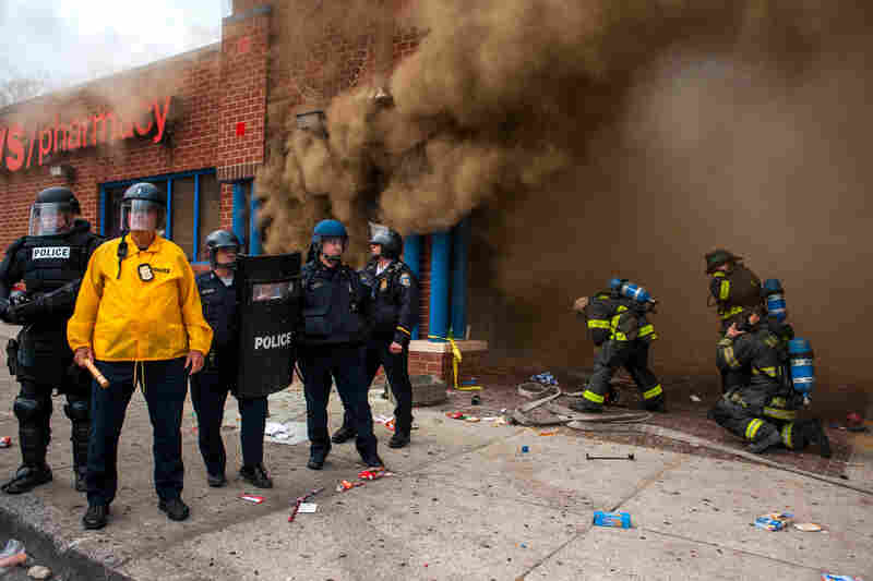 Police stand by a CVS that was on fire as firefighters arrive to fight the blaze in Baltimore.