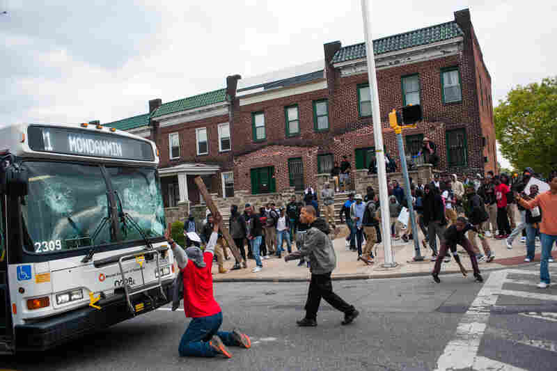 Demonstrators block a damaged bus at the Mondawmin Mall during a protest for the death of Freddie Gray in Baltimore.