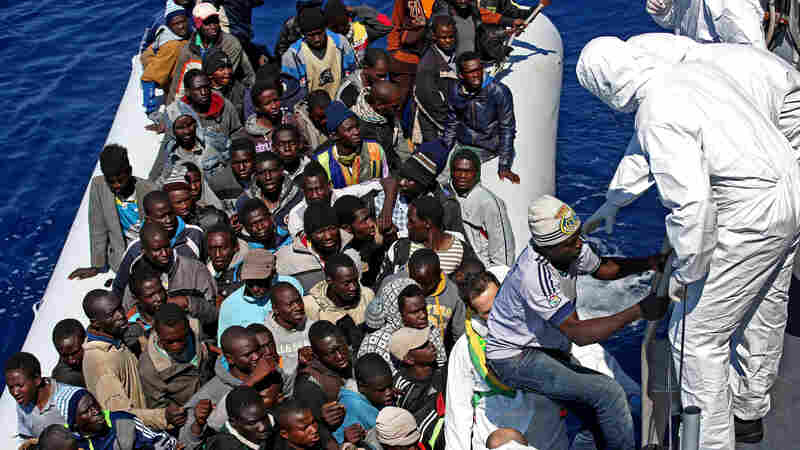 Migrants crowd an inflatable dinghy as members of the Italian coast guard approach them off the Libyan coast in the Mediterranean Sea on April 22.