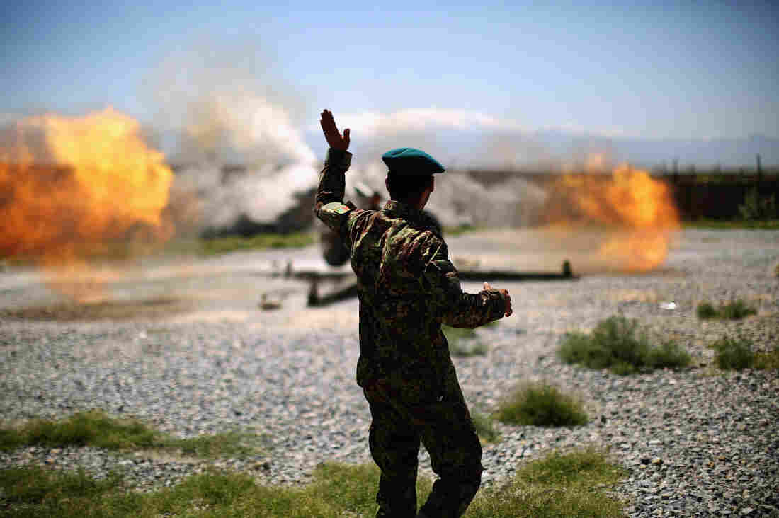 An artillery gun fires a round at Taliban fighters in the hills of Nangahar Province.