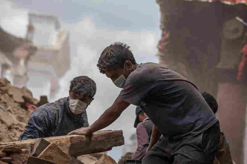 Volunteers clear debris of a collapsed temple at Basantapur Durbar Square in Kathmandu, Nepal on Monday. The devastating earthquake that hit Saturday is now blamed for at least 3,700 deaths.