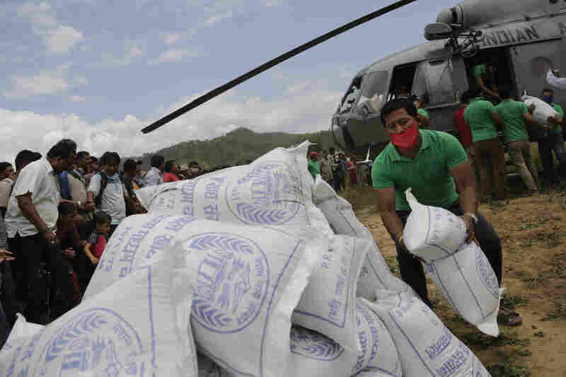 Nepalese volunteers unload relief material brought in an Indian air force helicopter for victims of the earthquake at Trishuli Bazar in Nepal. The earthquake has left nearly 1 million children in need of humanitarian aid, UNICEF says.