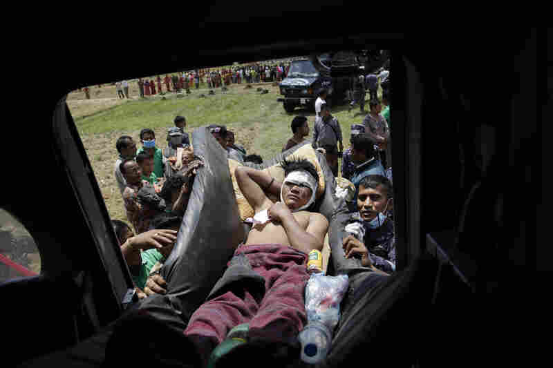 Nepalese soldiers carry a wounded man to an Indian air force helicopter as they evacuate victims from Trishuli Bazar to Kathmandu airport.