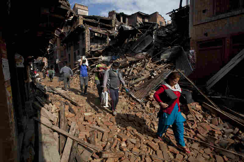 People carry belongings from their destroyed homes as they walk through debris in Bhaktapur, on the outskirts of Kathmandu.