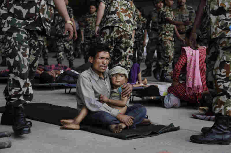 A man and child wait for ambulances after being evacuated at the airport in Kathmandu, Nepal, on Monday. The devastating earthquake that hit Nepal on Saturday is now blamed for at least 4,000 deaths.