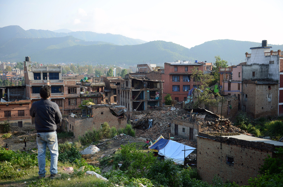 A man stands near collapsed houses in Bhaktapur, on the outskirts of Kathmandu, on April 27, two days after a magnitude-7.8 earthquake hit Nepal. Aftershocks tend to get less frequent with time, scientists say, but not necessarily gentler. (Prakash Mathema/AFP/Getty Images)