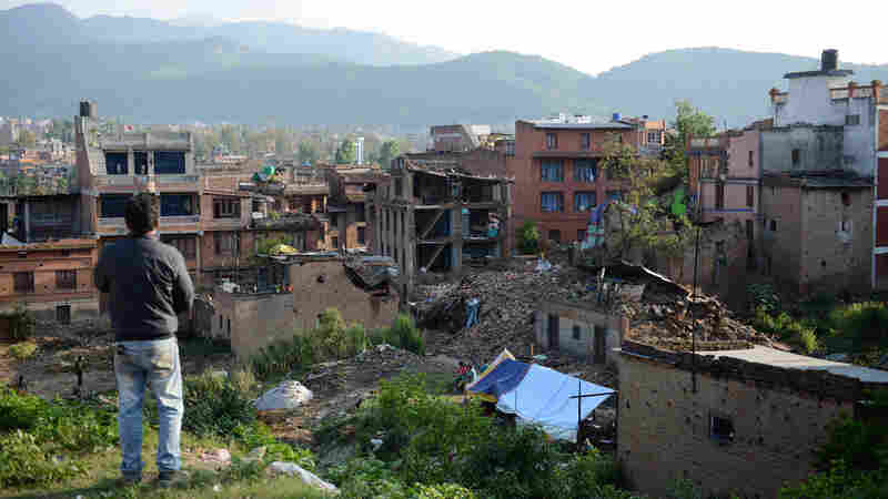 A man stands near collapsed houses in Bhaktapur, on the outskirts of Kathmandu, on April 27, two days after a magnitude-7.8 earthquake hit Nepal. Aftershocks tend to get less frequent with time, scientists say, but not necessarily gentler.