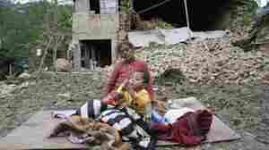 A woman and child rest in the open outside a destroyed building Sunday, a day after a major earthquake leveled homes in Kumalpur village on the outskirts of Kathmandu, Nepal. Nine people reportedly died in the small village, including four children.